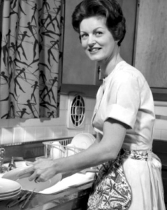 1960s woman housewife washing dishes in kitchen sink looking at camera